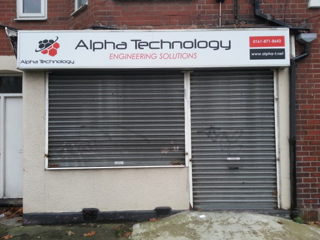Photo of Alpha Technology office with metal shutters rolled down.